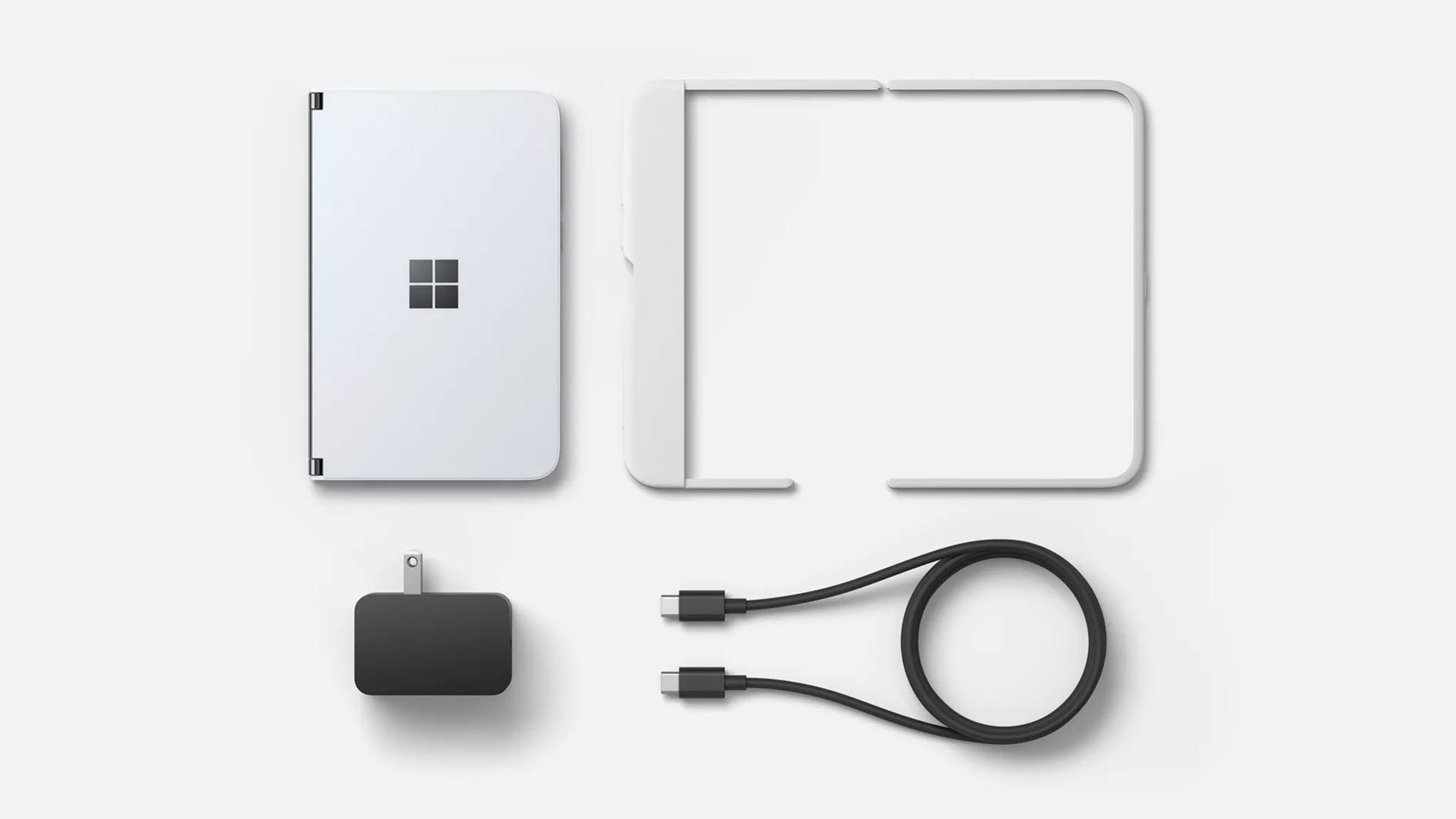 The Surface Duo phone, a charging cord and brick, and a bumper case.