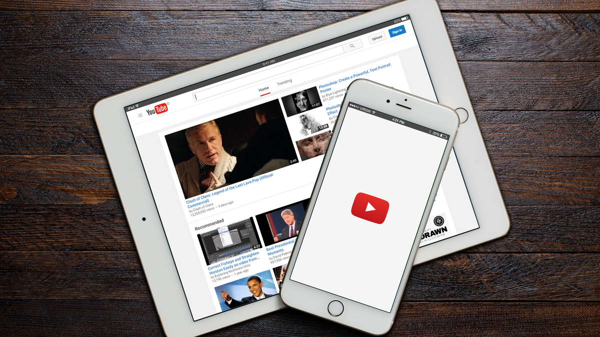 A loading screen of YouTube app on iPhone and landing page of YouTube website on iPad both sitting on a wooden table