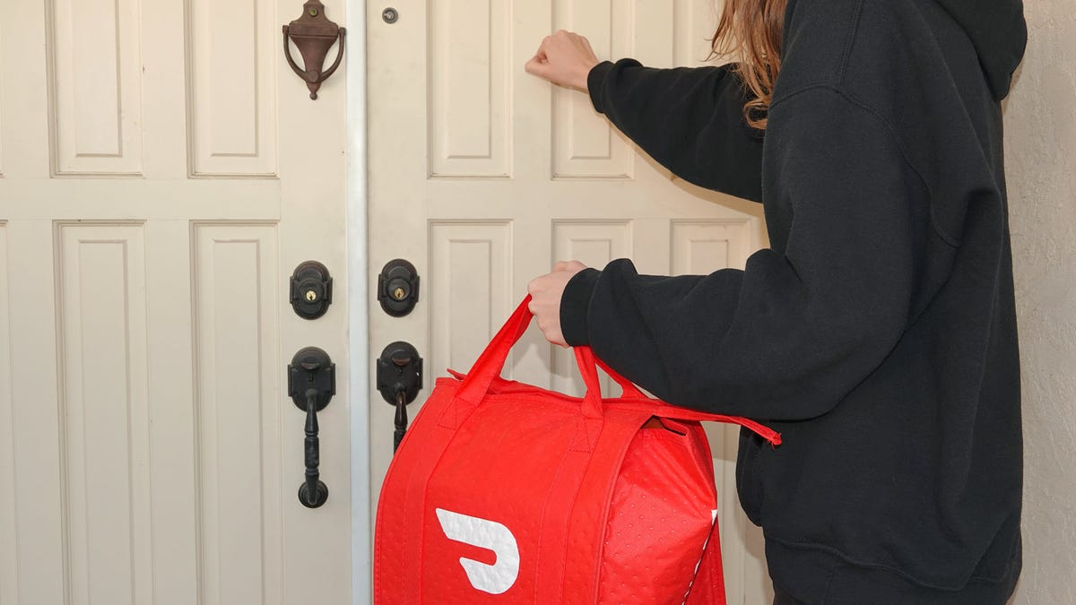 A person knocking on a door while holding a DoorDash branded bag.