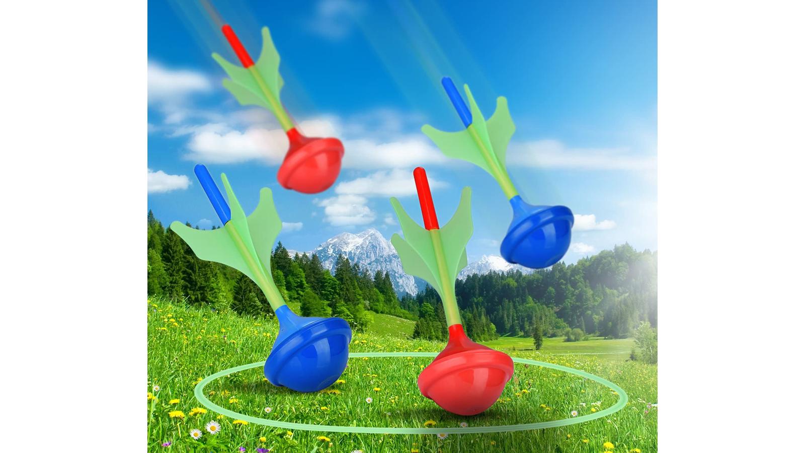 Lawn darts flying through the air towards glow in the dark target rings