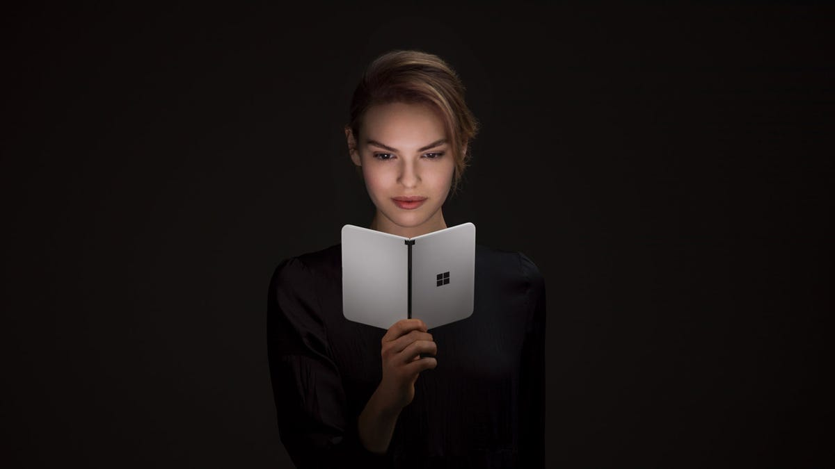 A woman looking at a Surface Duo