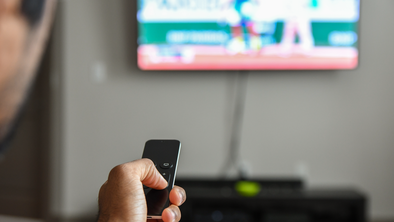 A man's hand using an Apple TV remote.