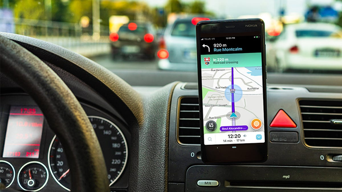 An Android phone mounted to a car dash and Displaying Waze