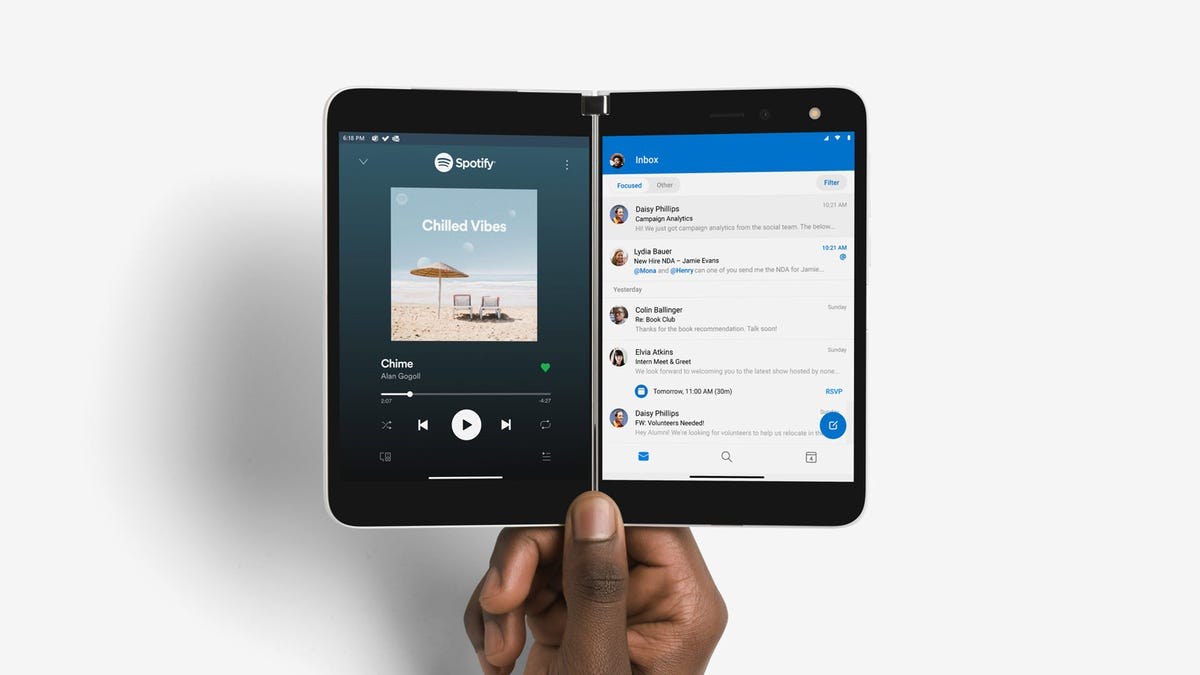 A Microsoft Surface Duo, with Spotify on one screen and Outlook on the other.