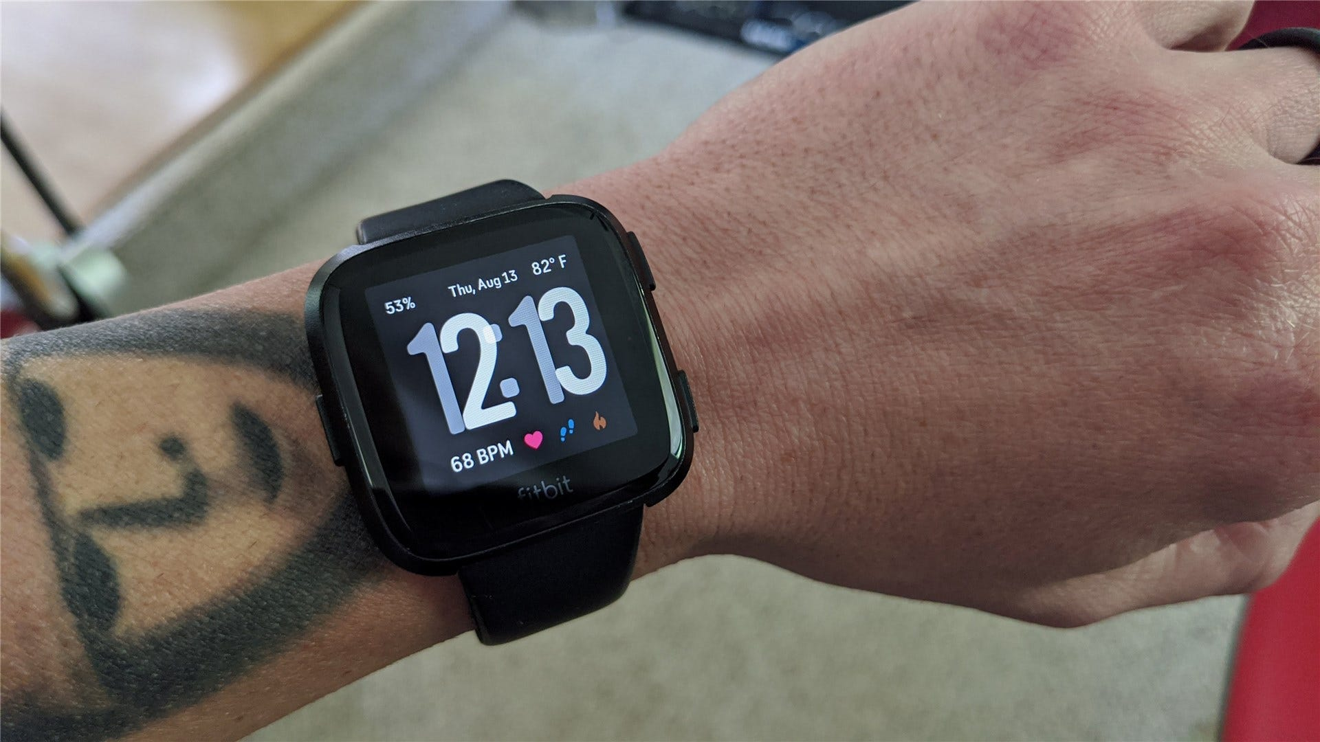 A fitbit versa showing time, weather, heart rate, and all other sorts of info