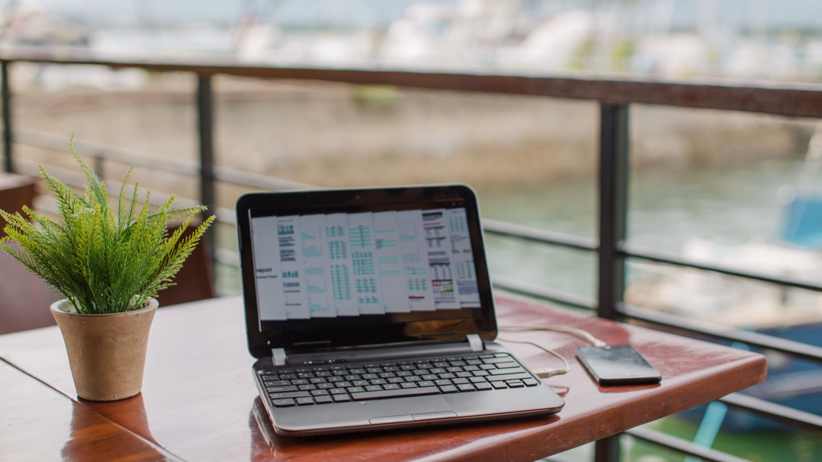 Laptop on wooden table at the yacht club cafe with online business via WiFi hotspot tethering