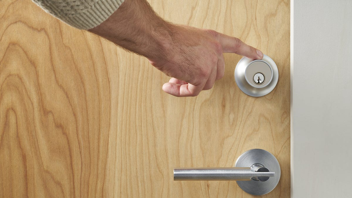 Someone touching a Level Touch smart lock.