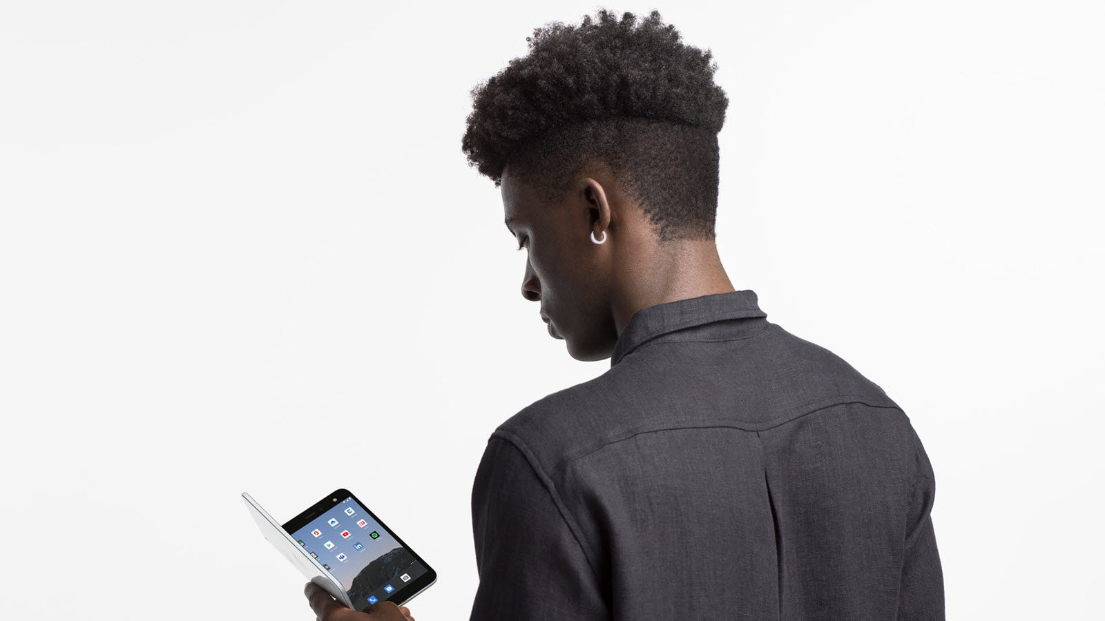 A man holding a Surface Duo and looking at the screen.