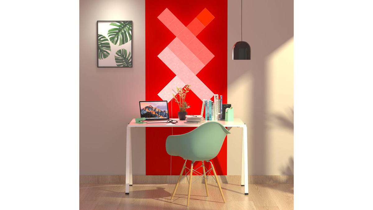 The Nanoleaf Canvas Smarter Kit light panels arranged on an office wall on a red background in a room with a desk and chair