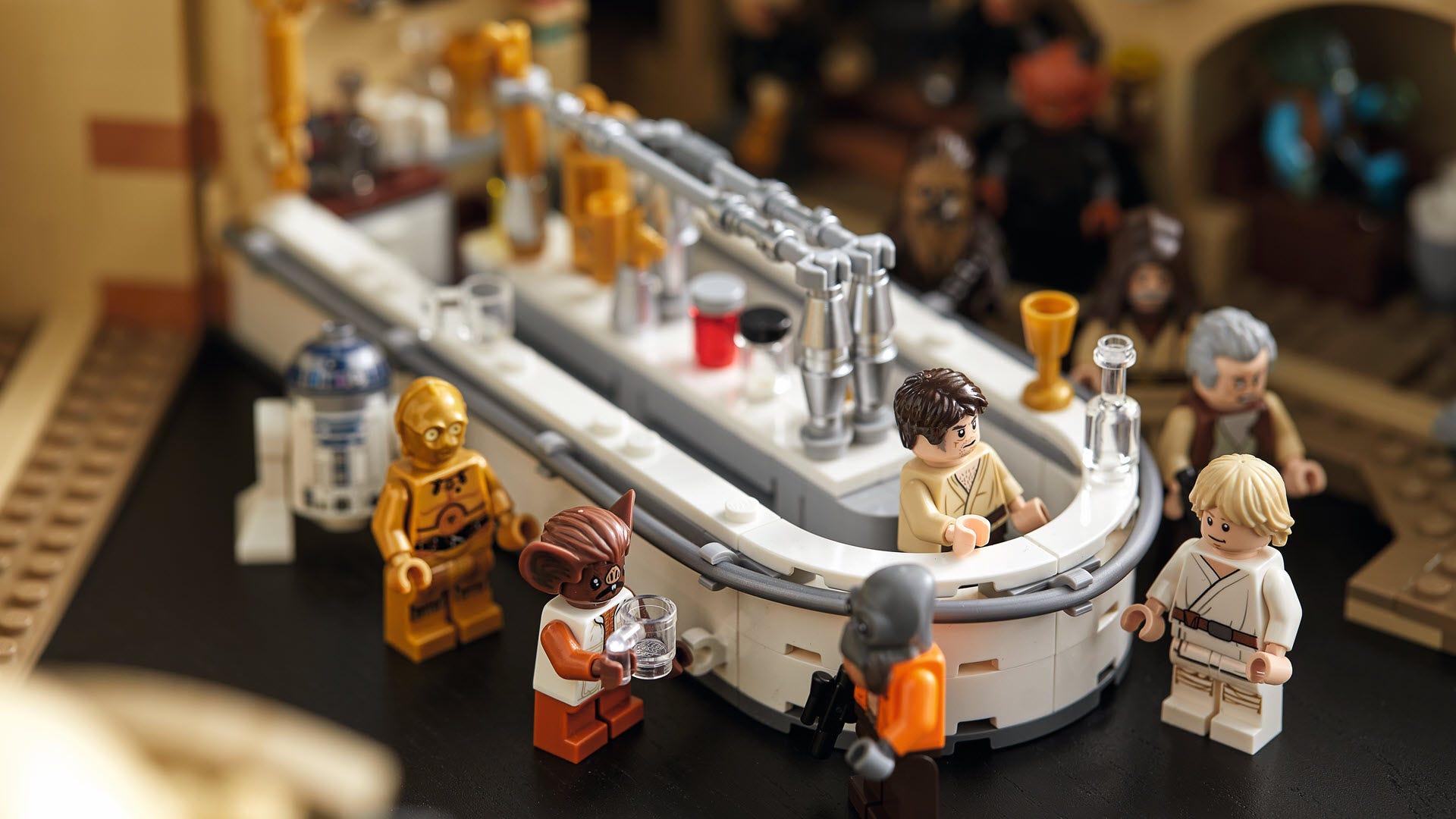 """A closeup of the Cantina bar with various """"Star Wars"""" minifgures standing around it."""