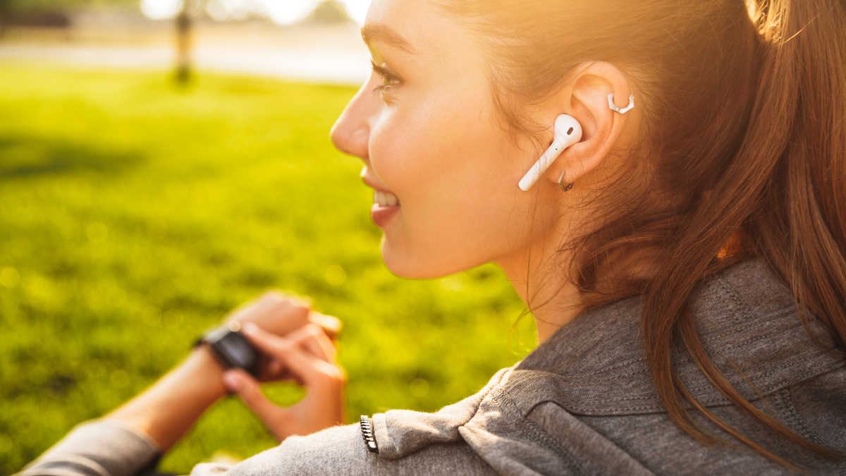 Sporty woman in 20s in sportswear using smartwatch and wireless earbuds while resting in a park