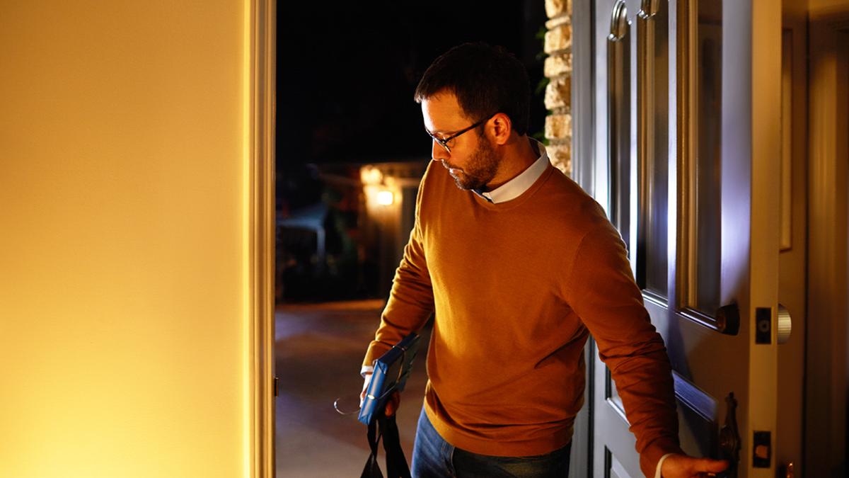A man entering a well-lit home.
