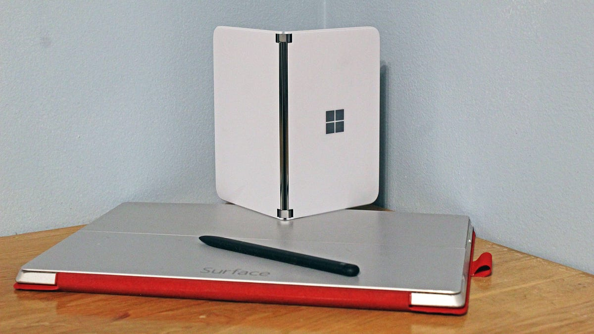 A Surface Duo on top of a Surface Pro 3 and Surface Slim Pen