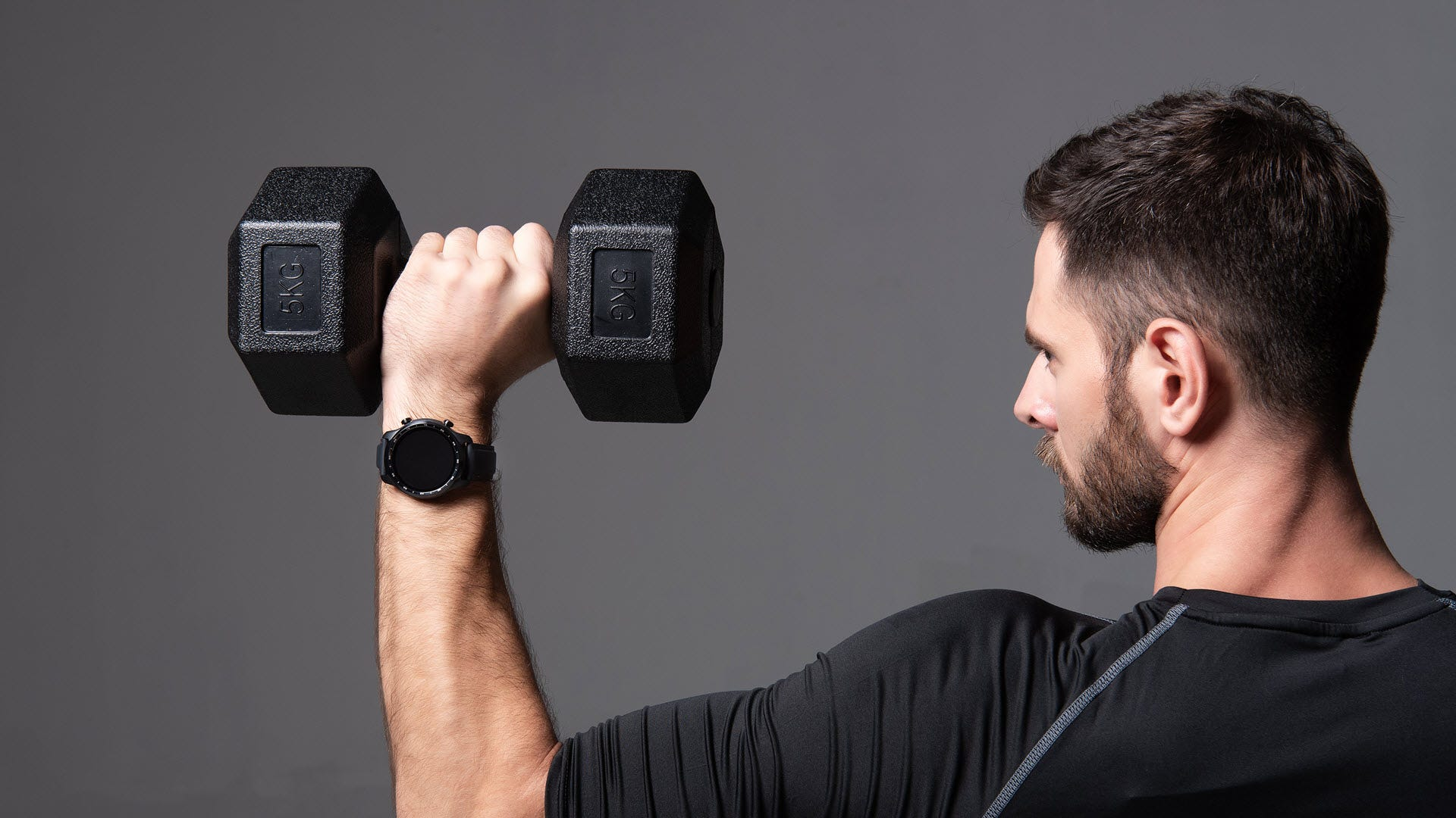 A man lifting weights while wearing a smartwatch.