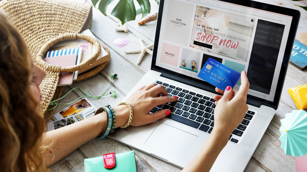 Summer beach holiday girl doing online shopping with credit card in hand