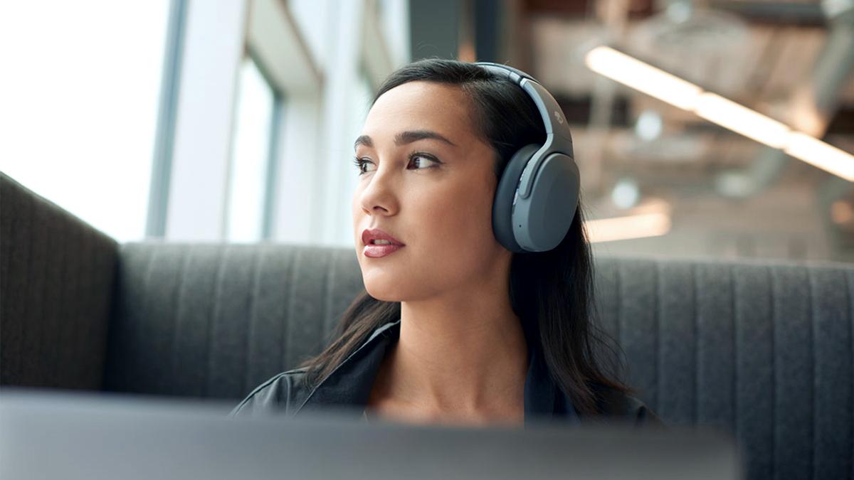 Girl on bus wearing Skullcandy Crusher Evo headphones