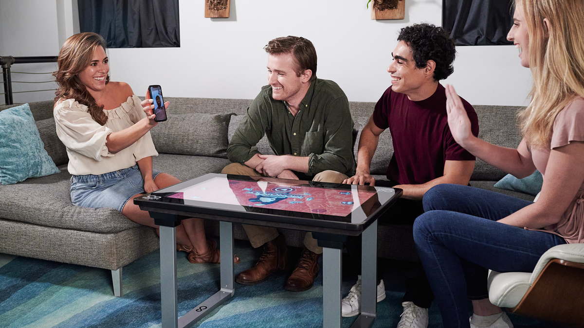 Four people sitting around a coffee table with a built-in touchscreen with a board game playing.
