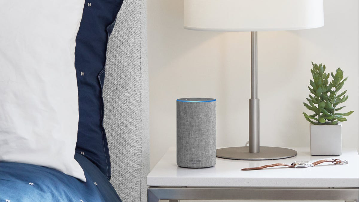 An Echo on a night stand next to a bed.