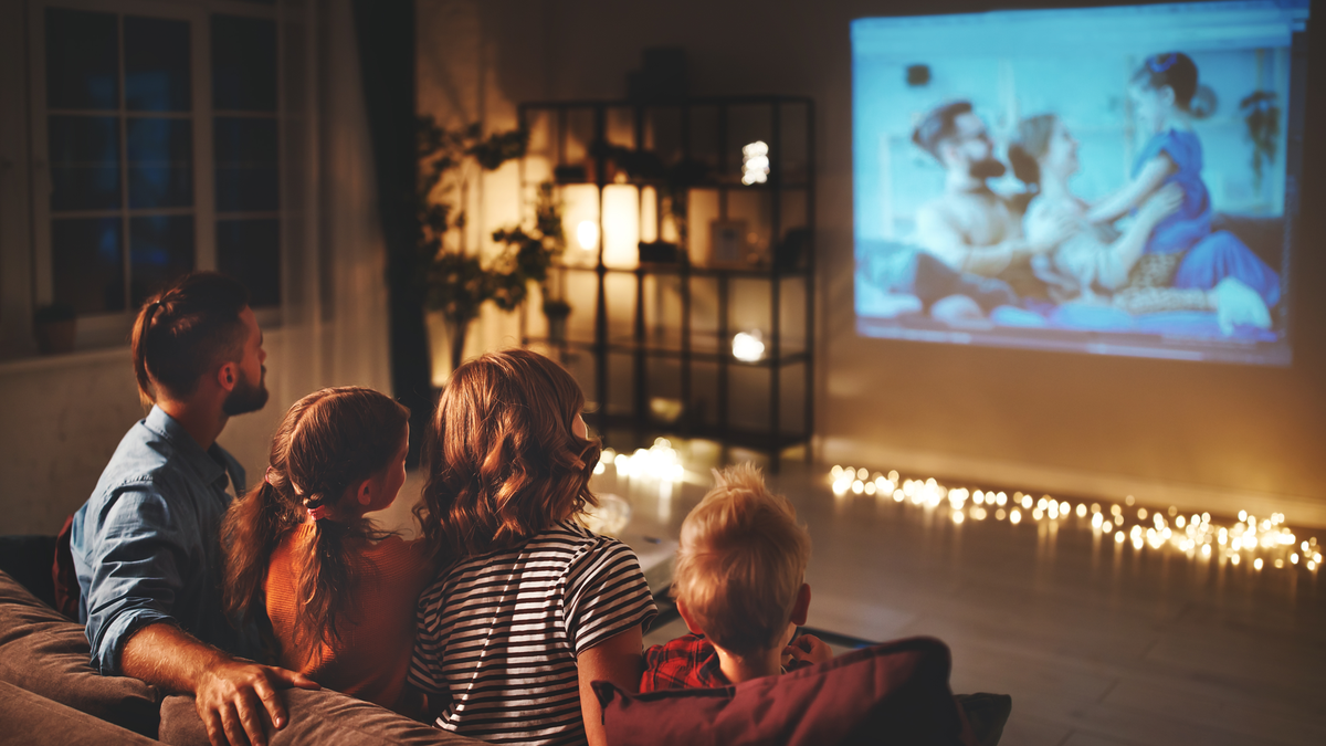family mother father and children watching projector TV movies with popcorn in the evening at home