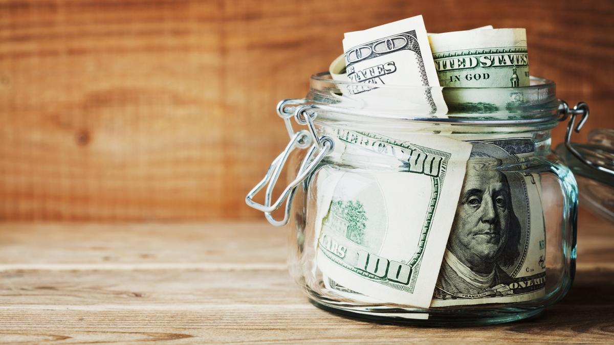 Hundred dollar bills in a glass jar on wooden background