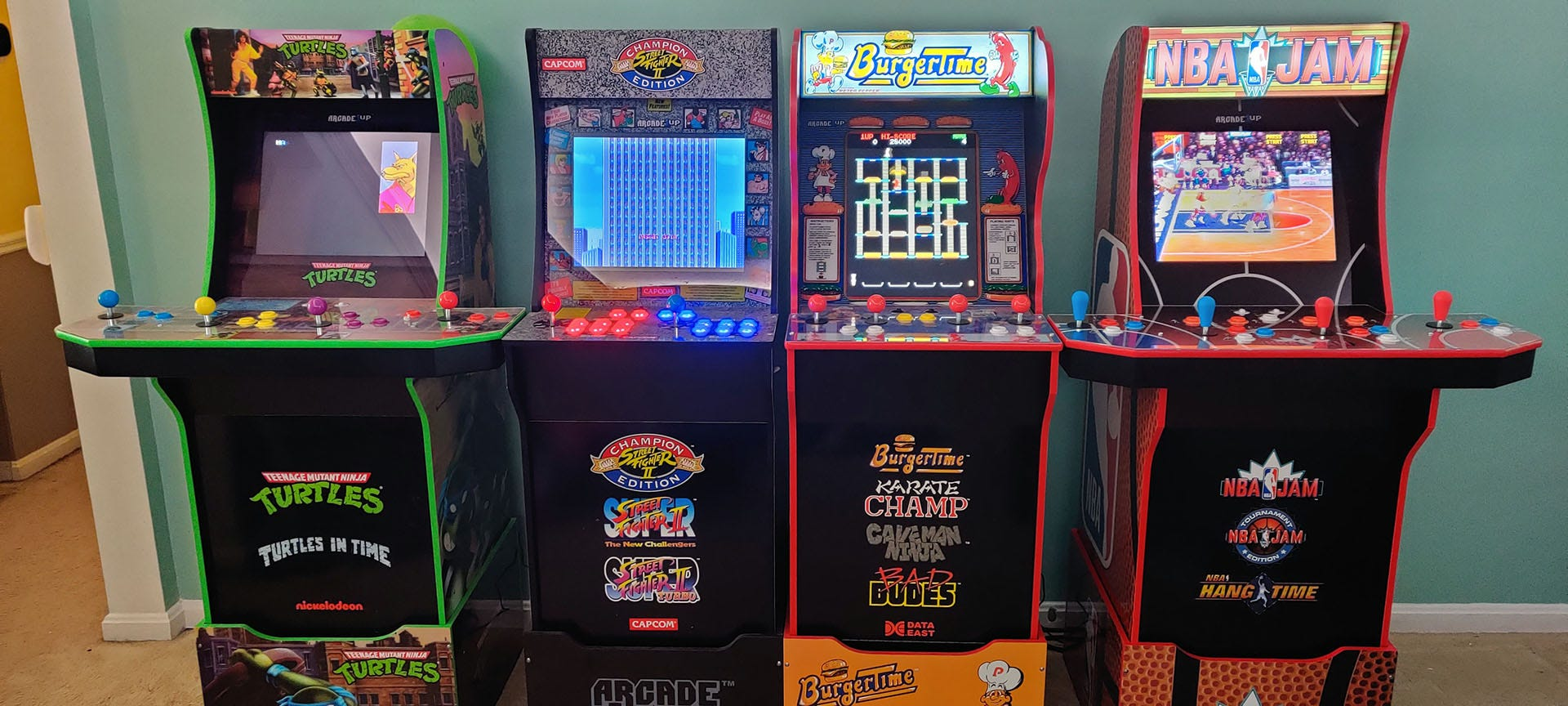 Four Arcade1Up machines standing in a row, all with nearly identical profiles.