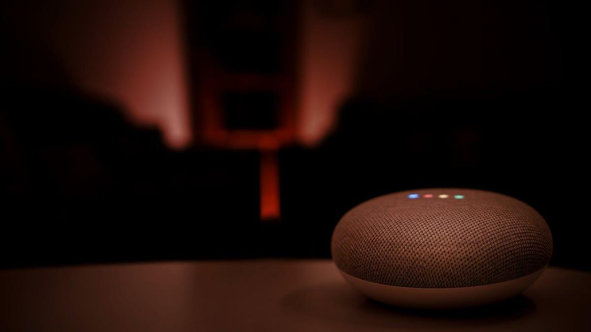 A Nest Mini smart speaker in a very dark room.