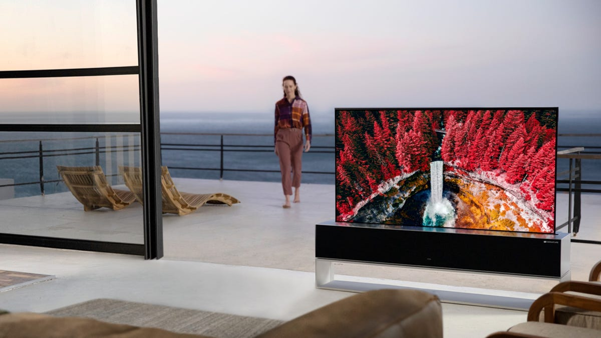 Woman standing next to LG OLED R TV