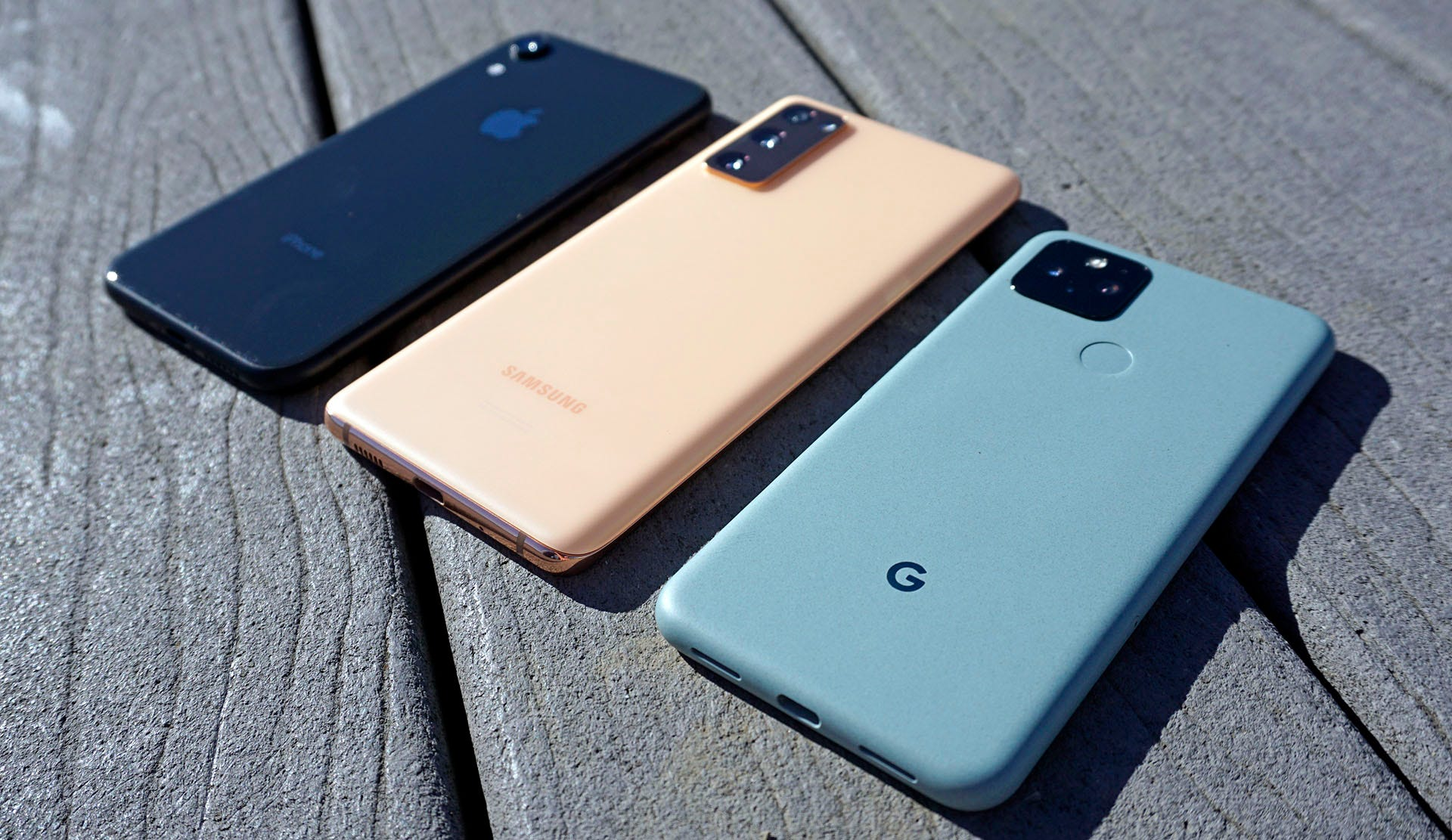 Comparing size: iPhone XR, Galaxy S20 FE, and Pixel 5, in a row on wood
