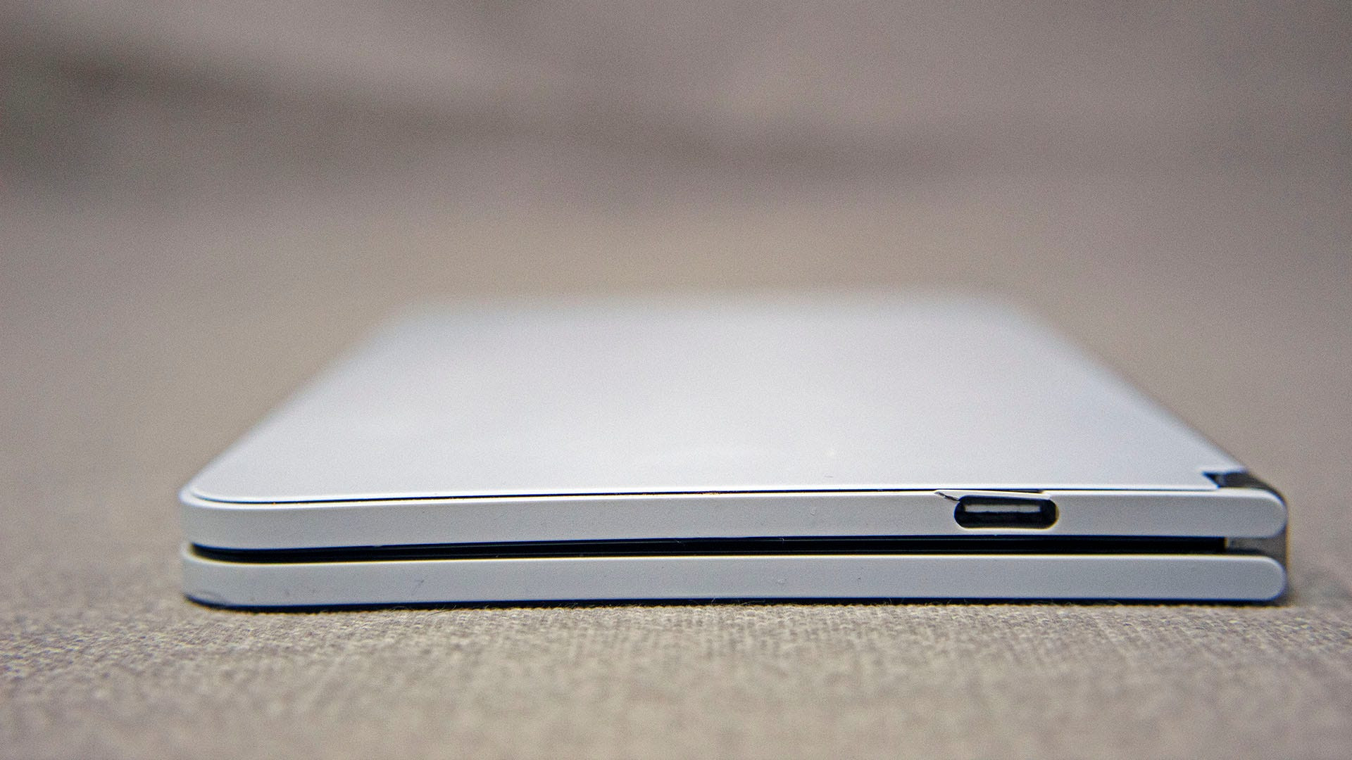 A closeup of a slightly bend Surface Duo with a cracked port.