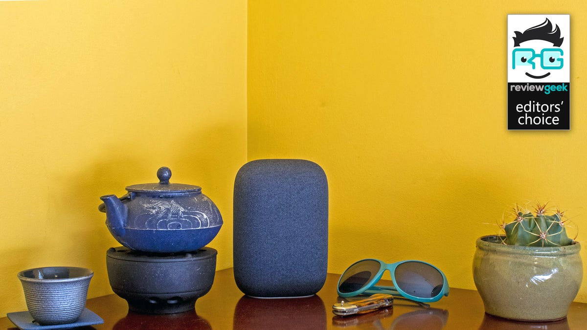A Nest Audio near a tea pot, cup, sunglasses and plant on a nightstand.