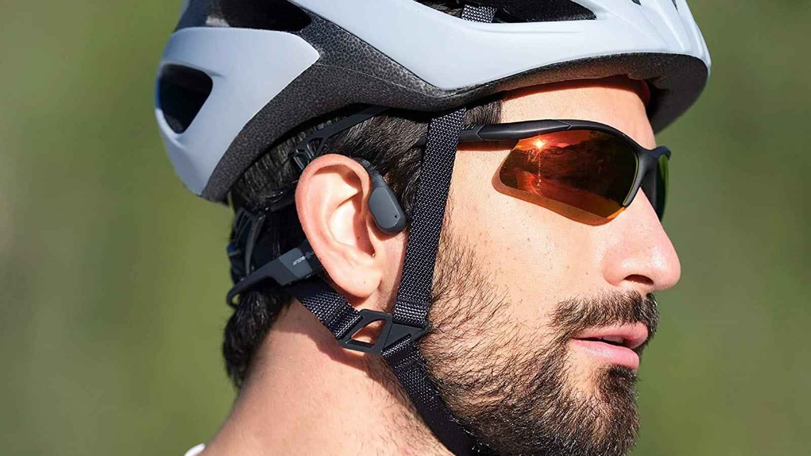 A man wearing the AfterShokz Mini headphones and a bike helmet.