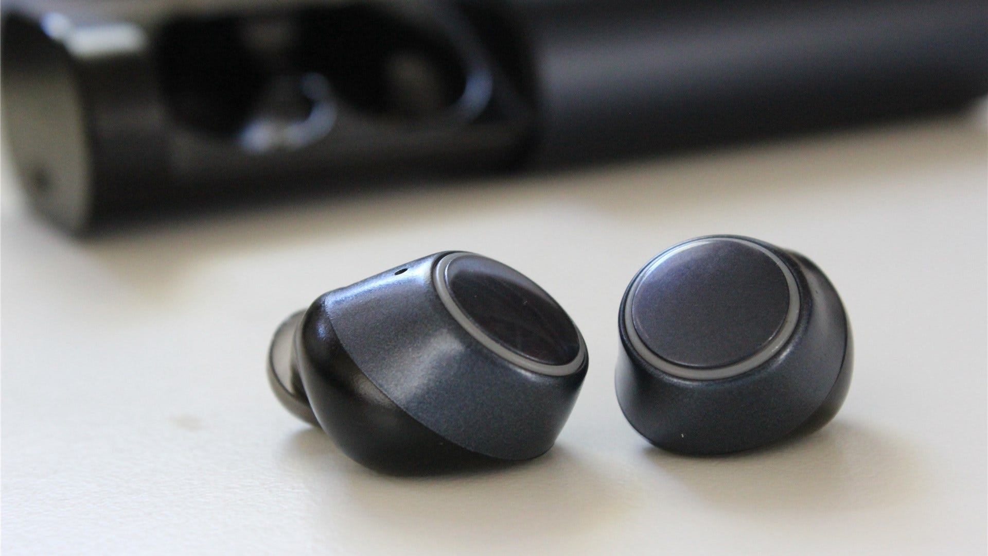 The Outlier Air v2 earbuds on a white desk with the case opened in the background