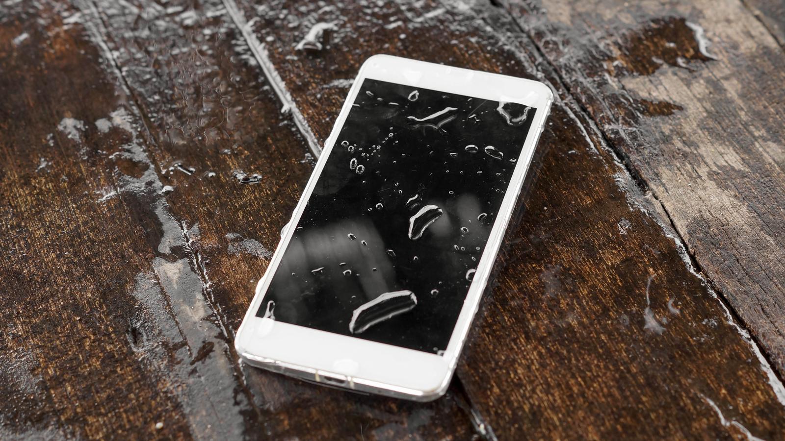 Wet smartphone on wood table