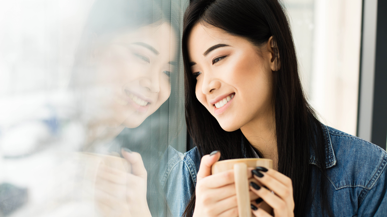 Person looking out window while holding coffee mug and smiling