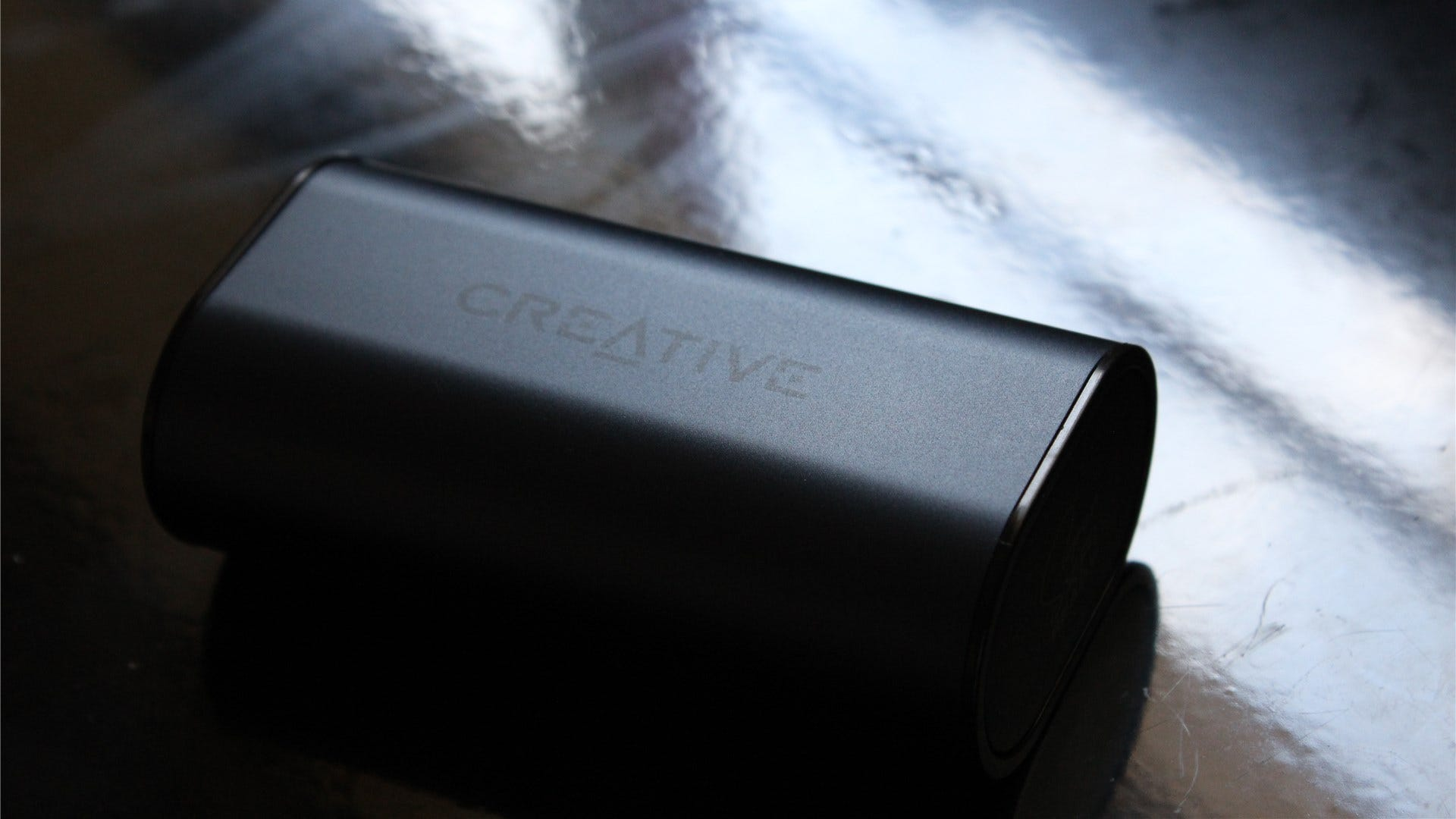The Creative Outlier Air v2 case in low light on a glossy black background
