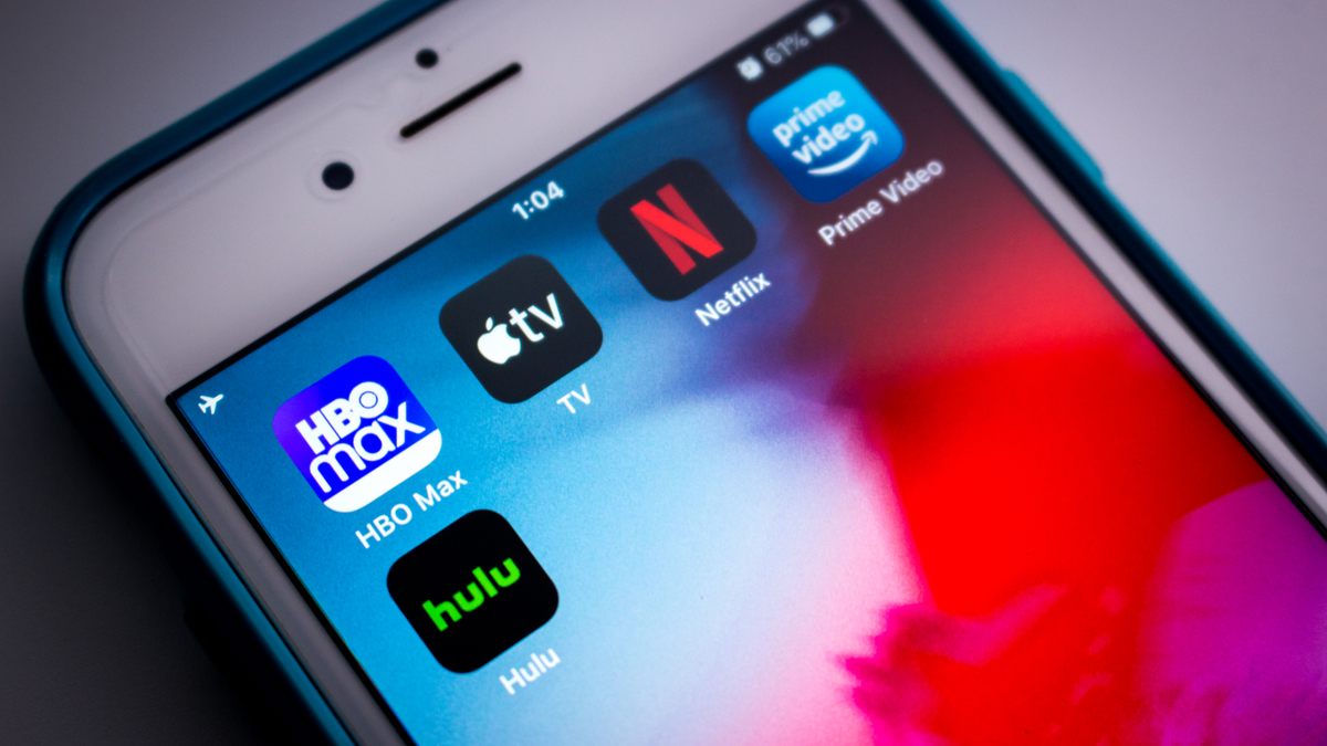 HBO Max, Apple TV, Netflix, Hulu, and Amazon Prime app logos on an iPhone