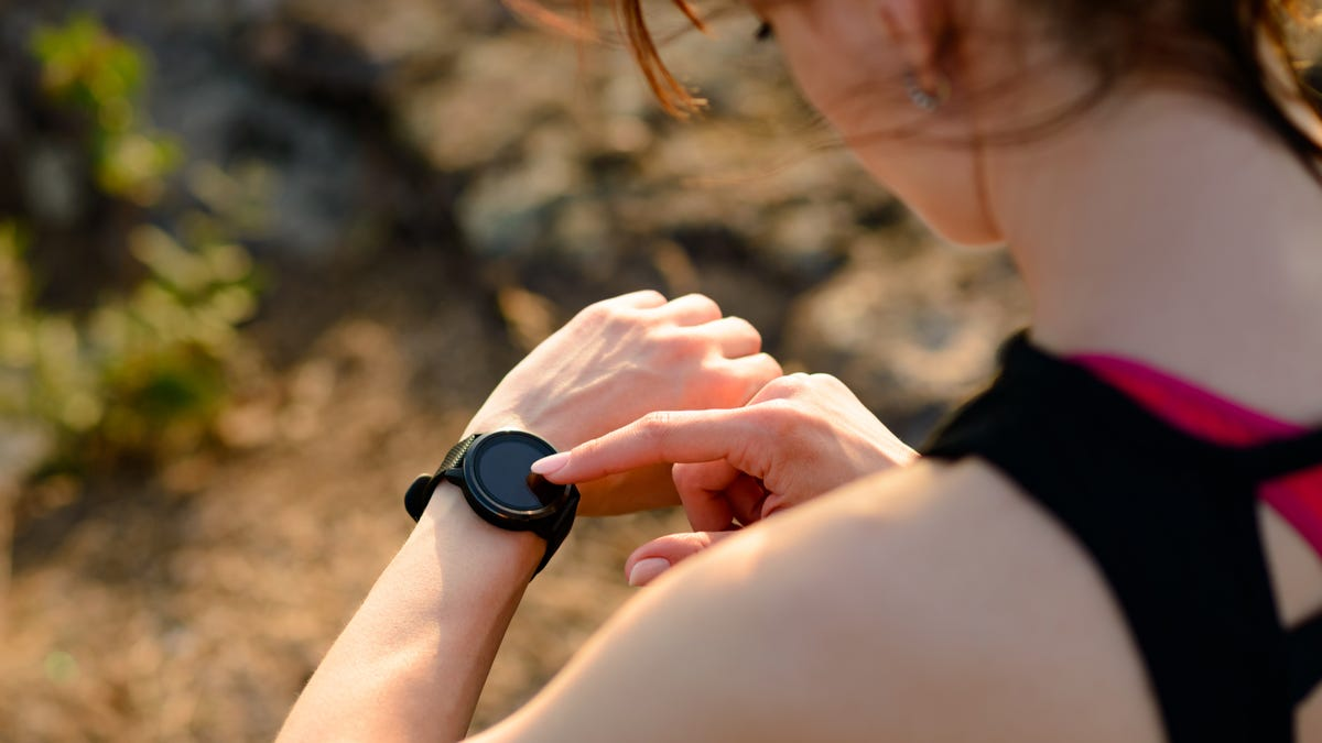 Young Woman Runner Using Multisport Smartwatch at Sunset on the Mountain Trail. Closeup of Hands with Fitness Tracker