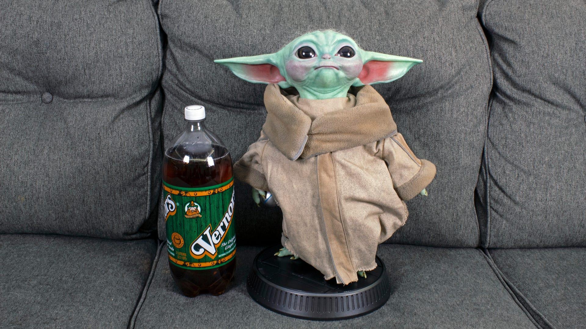 Baby Yoda standing taller than a 2-liter bottle of soda.