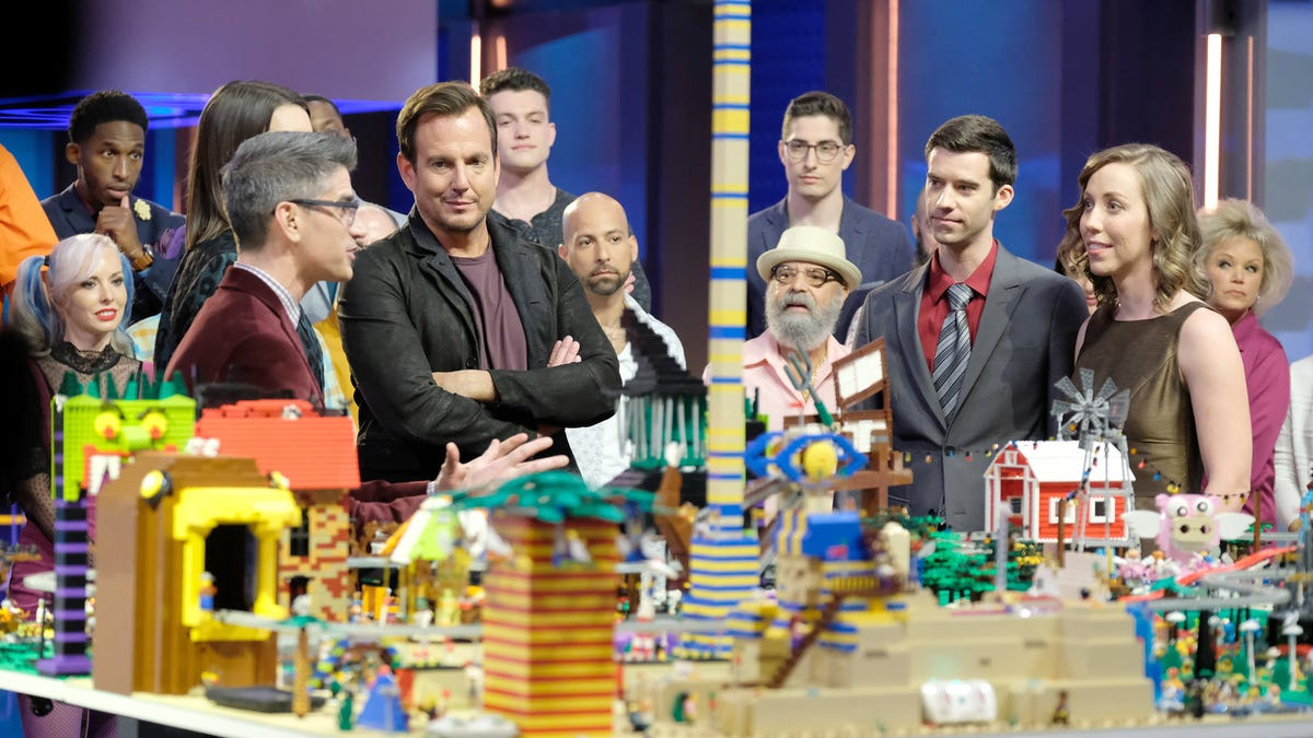 The original cast of 'LEGO Masters standing around a table full of LEGO bricks.