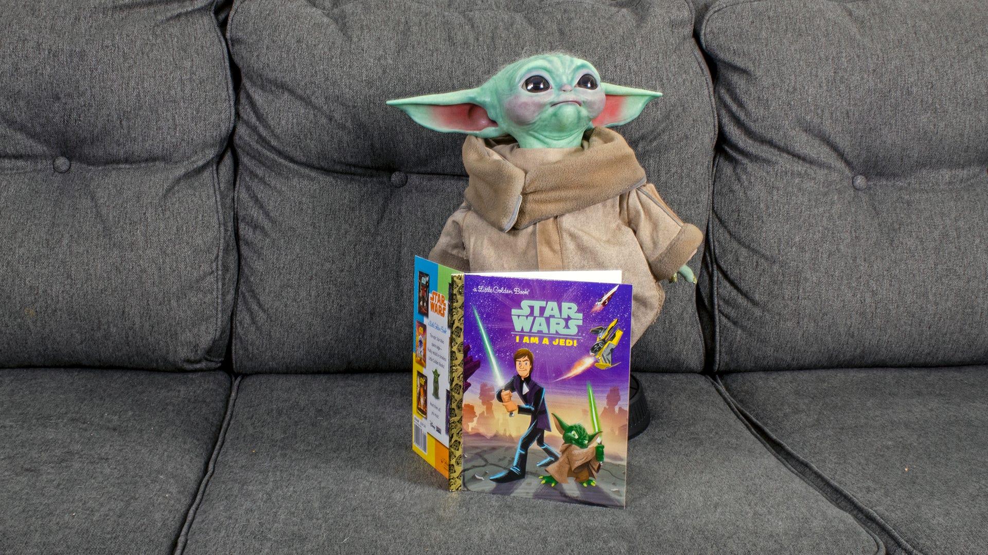 Baby Yoda next to a child's 'Star Wars' book.
