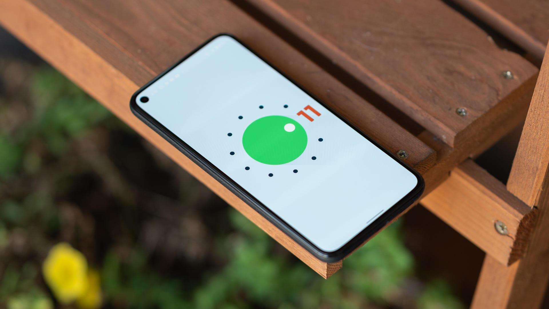 The Pixel 5 on a wooden table with the Android 11 easter egg screen.