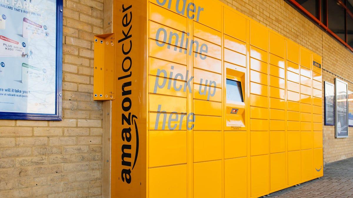 A yellow Amazon Locker system along a brick wall.