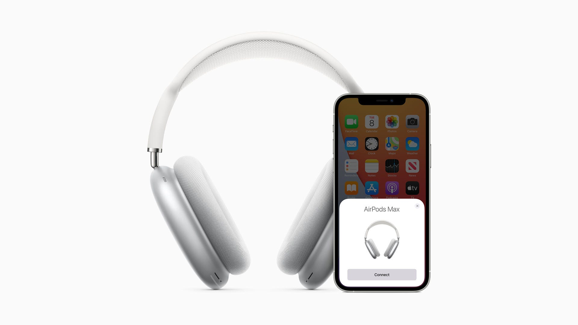 An AirPods Max headset next to an iPhone that is pairing with the headphones.