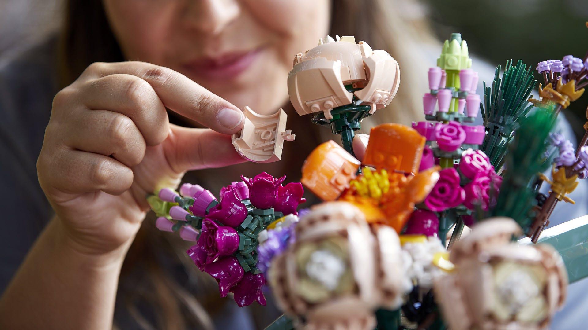 A person building a LEGO flower bouquet