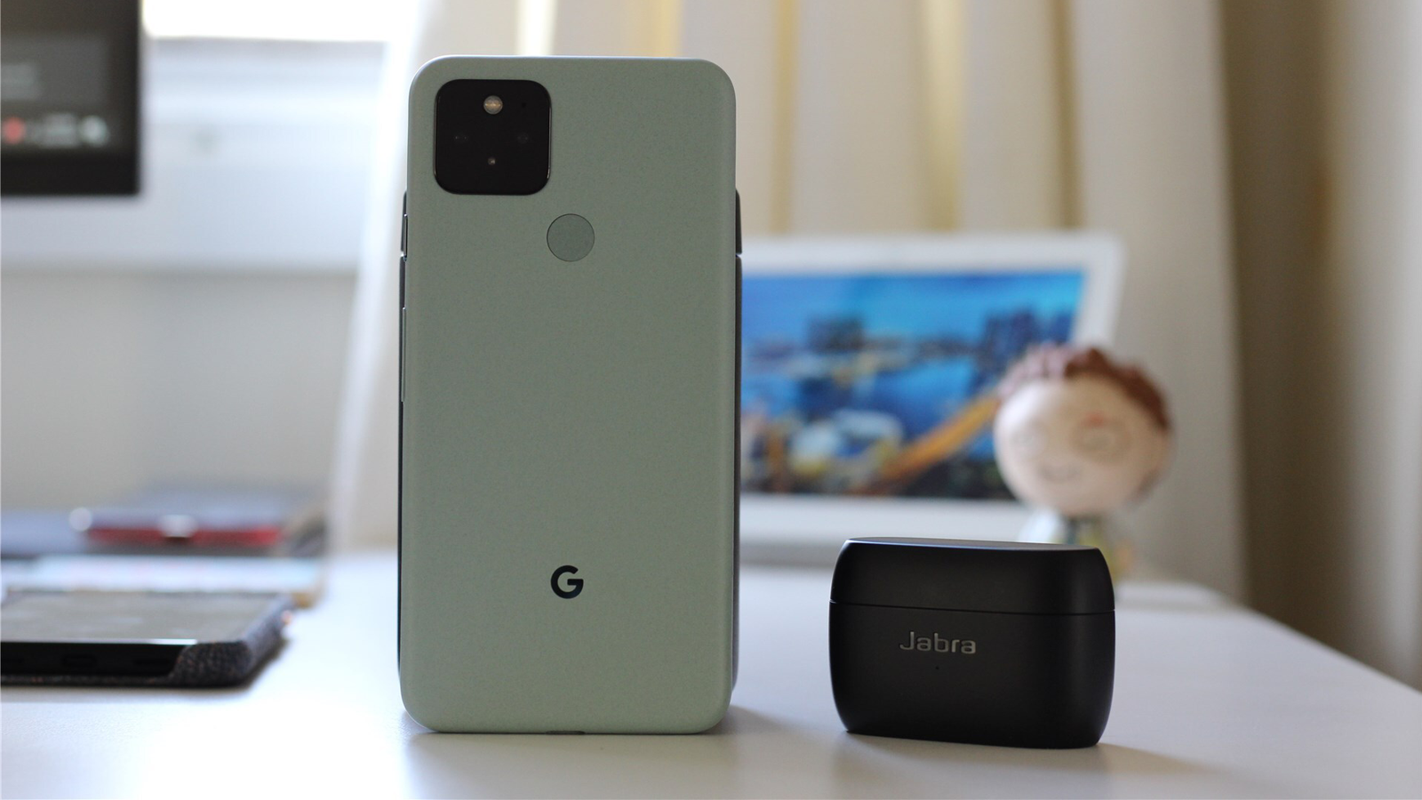 A green Pixel 5 with Jabra Elite 85t beside it and Nest Hub in the background