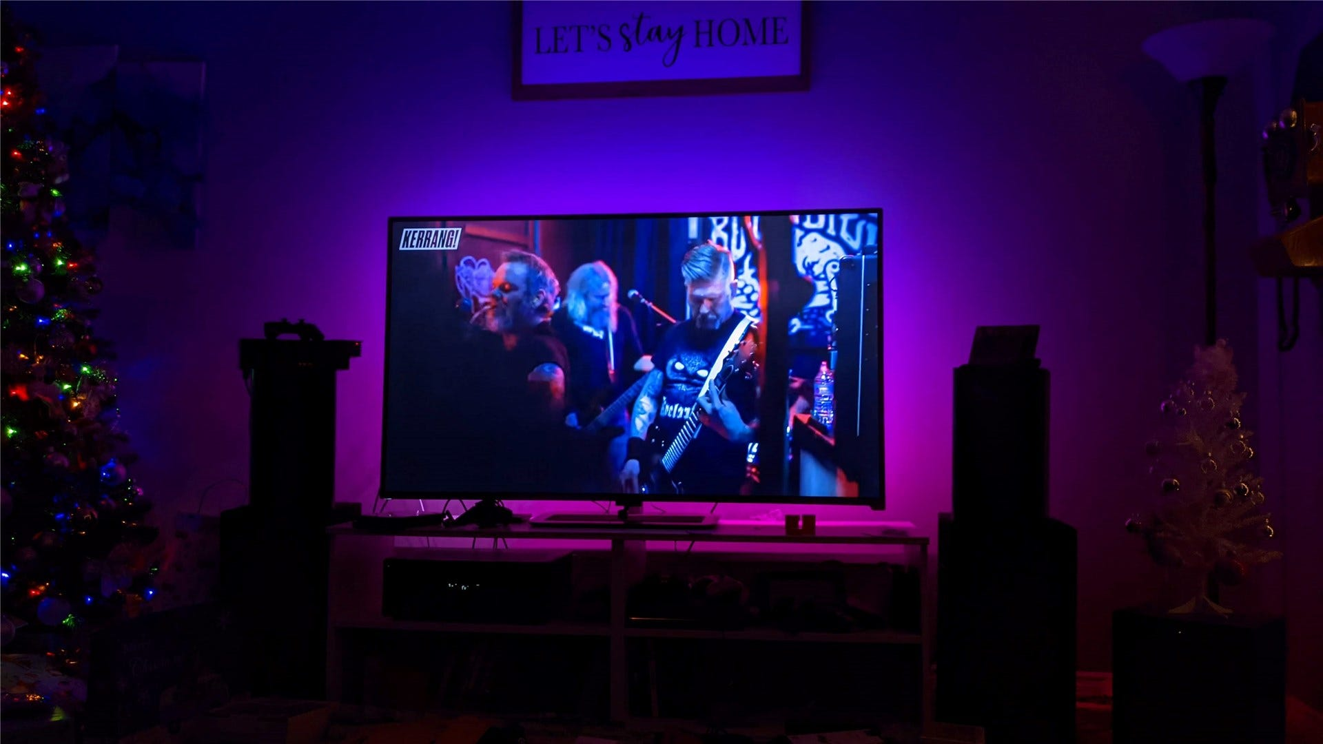 The Immersion glowing blue, purple, and pink behind a TV showing a live concert