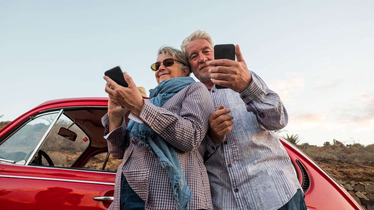 Happy elderly senior couple using smartphones outdoors near a beautiful retro red car