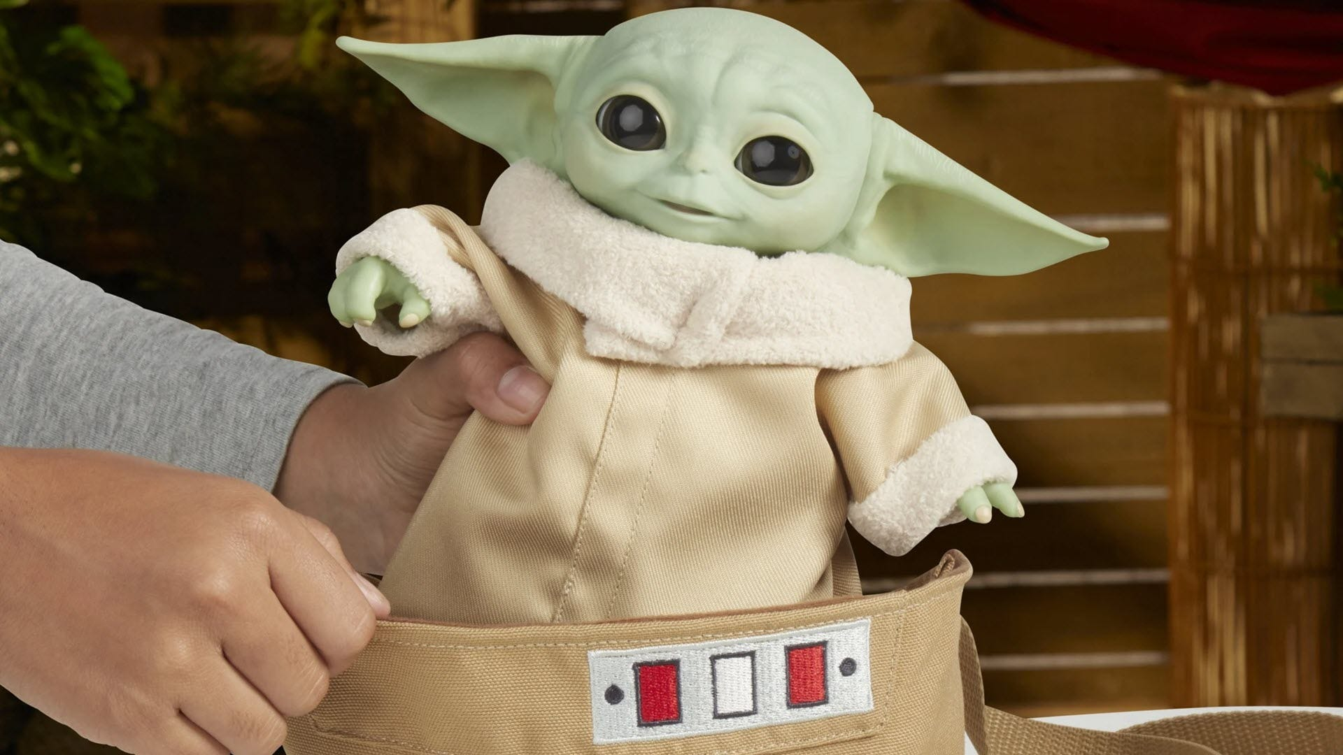 An Animatronic Baby Yoda in a cloth carrying bag.