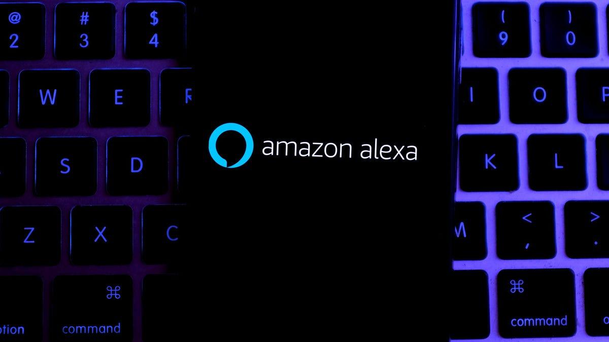 Amazon Alexa on an iPhone resting on a MacBook keyboard.