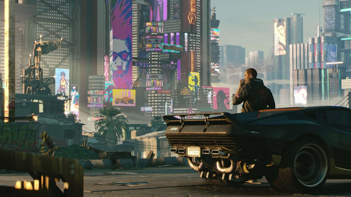 A game still from Cyberpunk 2077: man smokes while leaning on car in front of city